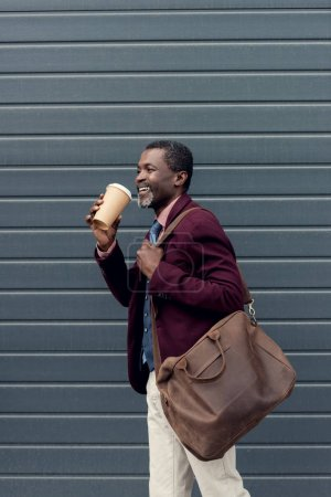 fashionable african american man with leather bag and disposable cup of coffee