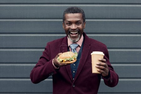 excited stylish african american man with coffee to go and hamburger
