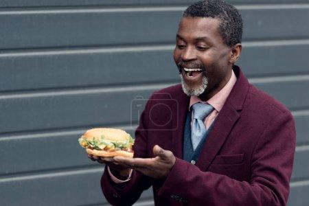 Photo pour Excité homme afro-américain regardant hamburger savoureux - image libre de droit