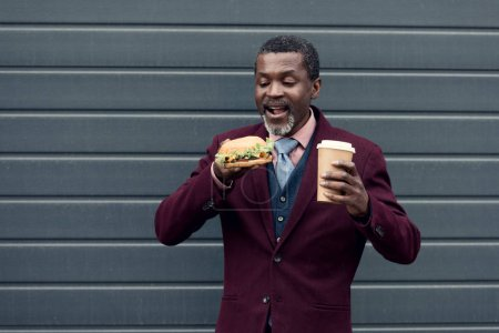 stylish african american man with disposable cup of coffee and yummy hamburger