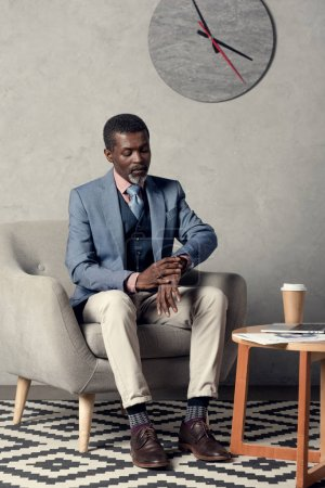 stylish african american businessman looking at wristwatch while sitting at table with coffee