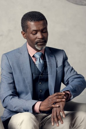 middle aged african american businessman looking at watch