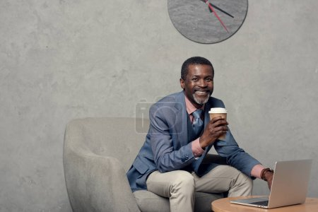 smiling african american man in blue jacket with coffee and laptop