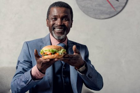 cheerful middle aged african american man with hamburger