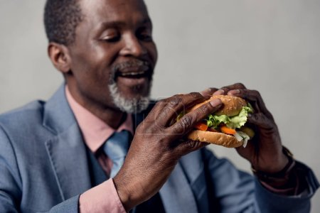 middle aged african american man with hamburger