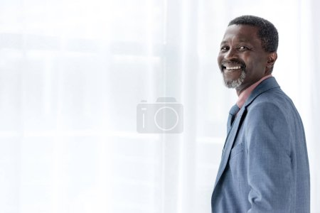 mature cheerful african american man in blue jacket