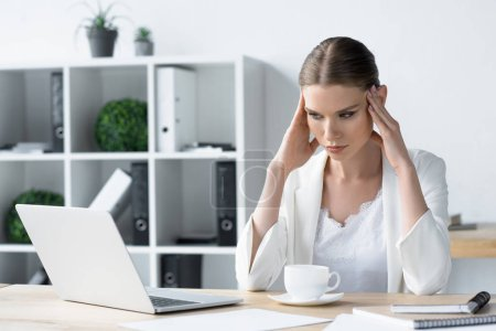 overworked young businesswoman with headache sitting at workplace in office and holding head
