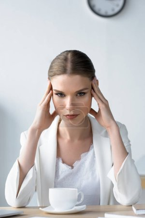 suffering young businesswoman with headache sitting at workplace in office and holding head