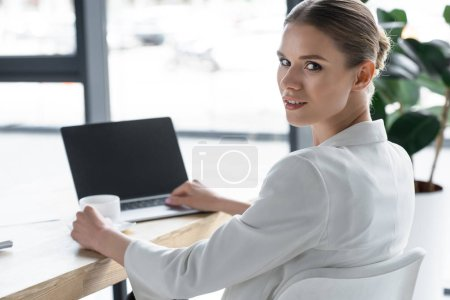 successful young businesswoman working with laptop at modern office