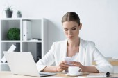 beautiful young businesswoman using smartphone at office