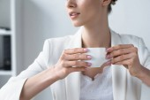 cropped shot of young businesswoman drinking coffee at office
