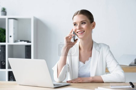 Photo for Happyyoung businesswoman talking by phone at office - Royalty Free Image