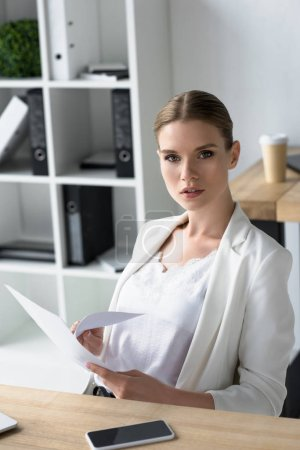 attractive young businesswoman doing paperwork at office and looking at camera