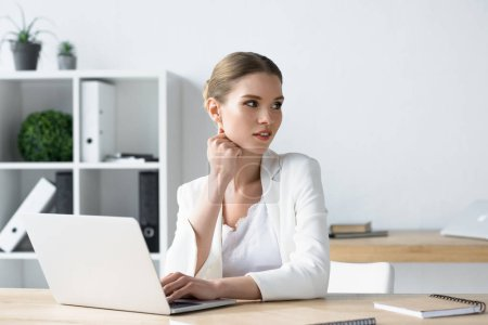 beautiful young businesswoman working with laptop at office and looking away