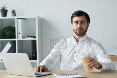 confident young businessman with laptop and coffee to go looking at camera