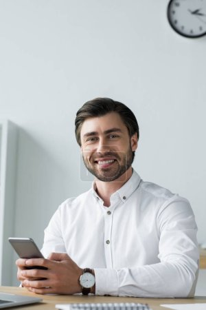 happy young businessman using smartphone at workplace and looking at camera