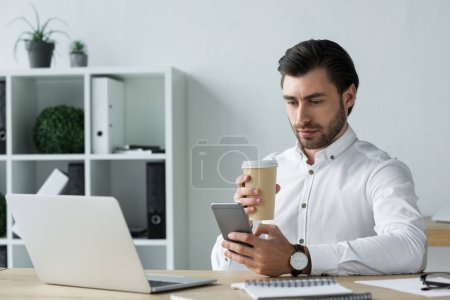 handsome young businessman with paper cup of coffee using smartphone at workplace