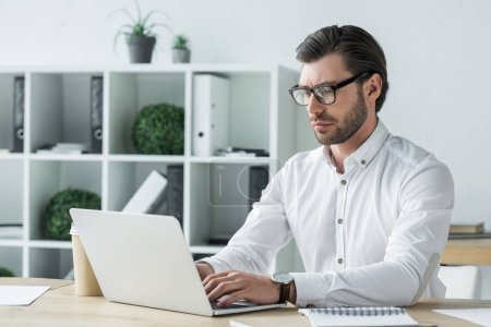 confident young businessman working with laptop at modern office