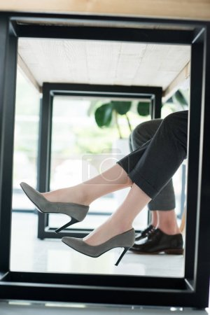 cropped shot of managers in stylish shoes at office