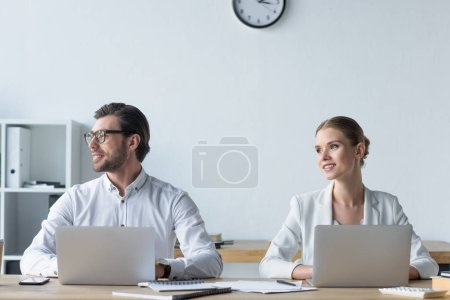 young managers working with laptops together at office and looking away