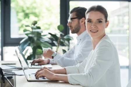 side view of young attractive managers working with laptops together at office