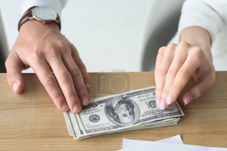 cropped shot of business partners holding stack of cash on table
