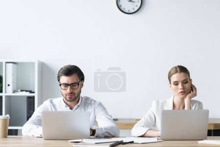 Photo for Concentrated young managers working with laptops together at office - Royalty Free Image
