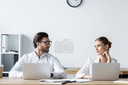 Photo for Managers working with laptops together at office and looking at each other - Royalty Free Image