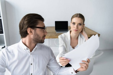 successful young managers doing paperwork together at modern office