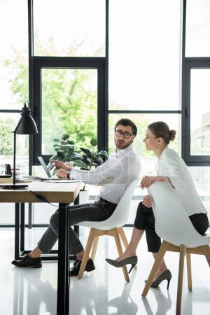 side view of young attractive managers working together at modern office