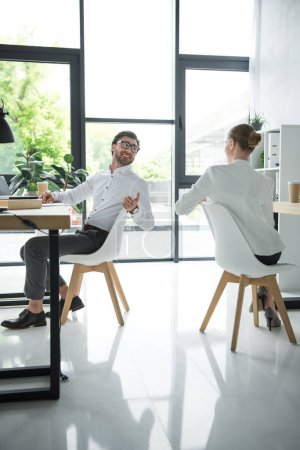 happy young managers talking at workplace in modern office