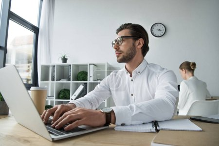 close-up shot of handsome young businessman working with laptop at office with blurred colleague on background