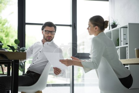 confident businesspeople passing documents at workplace in office