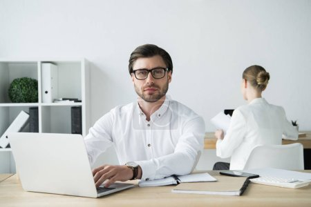 handsome young businessman working with laptop at modern office with colleague sitting on background