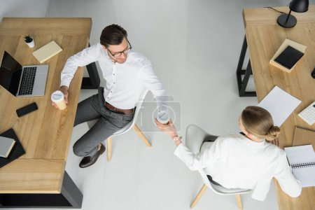 overhead view of young business colleagues with paper cups of coffee sitting at office