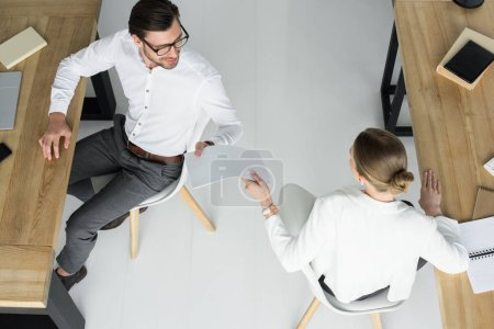 overhead view of businesspeople passing papers on workplace at office