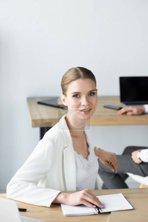 beautiful young businesswoman sitting at workplace with notebook