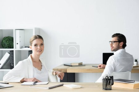 young business colleagues sitting at workplace in office