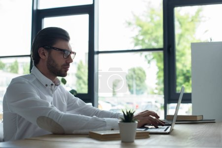 successful young businessman working with laptop at modern office