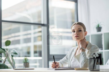 Photo for Beautiful young businesswoman sitting at workplace in modern office and looking at camera - Royalty Free Image