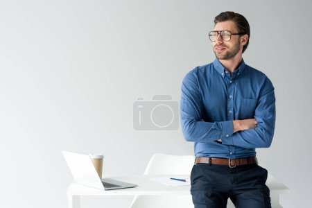 Photo for Handsome young businessman with crossed arms leaning back at workplace isolated on white - Royalty Free Image