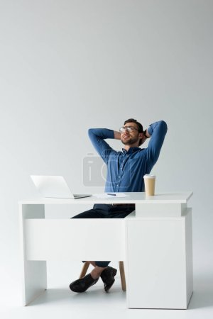 handsome young businessman relaxing at workplace on white