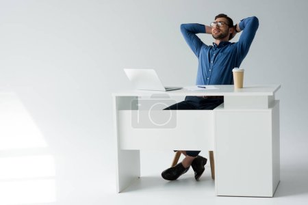 happy young businessman relaxing at workplace on white