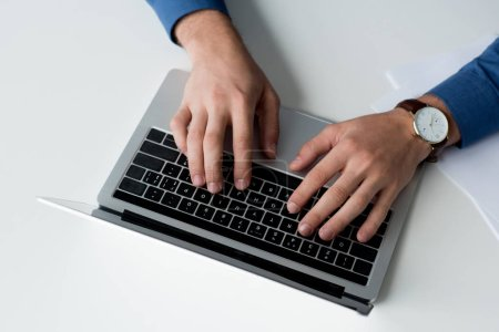 cropped shot of man working with laptop on white surface