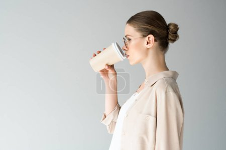 side view of beautiful young woman drinking coffee to go isolated on grey