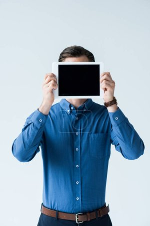 stylish man covering face with tablet with blank screen isolated on white