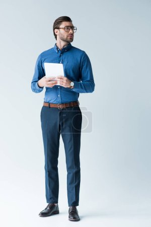confident young man in stylish clothes with tablet on white