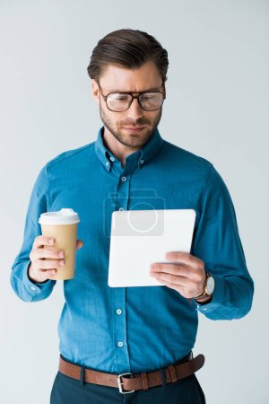 focused young man with paper cup of coffee using tablet isolated on white