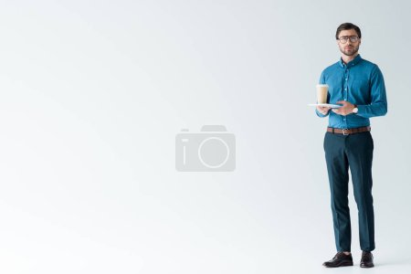 handsome young man with paper cup of coffee and tablet on white
