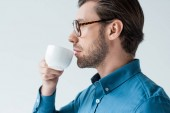 side view of young man drinking coffee from cup isolated on white